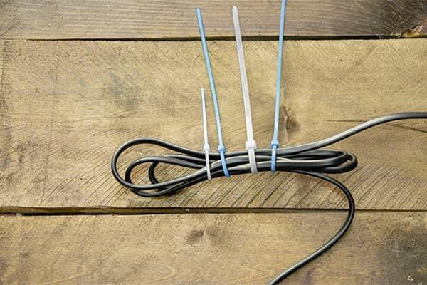 Auf einem braunen Holzbrett liegt ein Kabel, welches mit vier Kabelbindern ordentlich zusammengebunden ist.