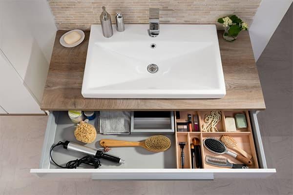 Sicht von oben auf einen braunen Waschtischunterschrank mit weißem Waschbecken. Die Schublade ist offen. Darin sind verschiedene Bürsten, Pinsel, Rasierer und Seifenstücke zu sehen.