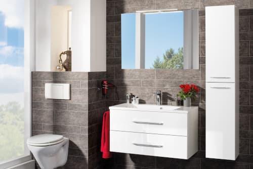 Weiße Badmöbel, bestehend aus einem weißen Waschtisch und Hochschrank. Über dem Waschplatz befindet sich ein Spiegel.