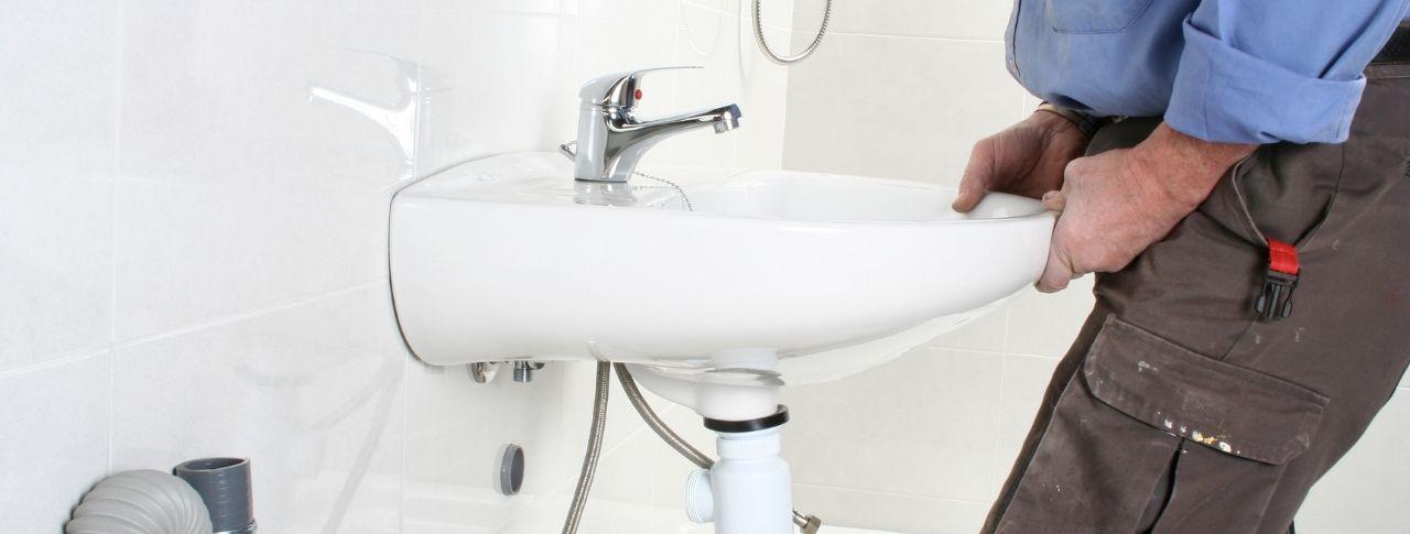 Ein Mann in Arbeitskleidung bringt ein Waschbecken an der weißen Fliesenwand an.