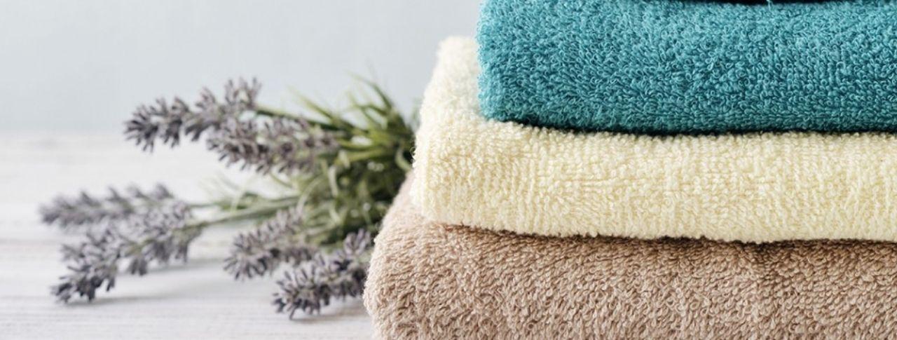 Neben einem Stapel gefalteter Handtücher liegt ein Strauß Lavendelblüten.