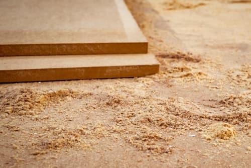 Zwei MDF-Platten liegen aufeinander. Rechts daneben liegen Holzfaserreste, aus denen eine MDF-Platte besteht.