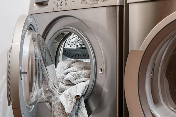 Beige Handtücher in der Trommel einer grauen Waschmaschine.