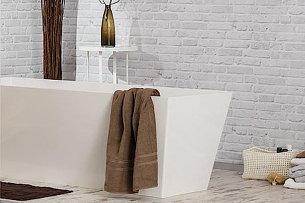 Ein braunes Handtuch hängt über einer weißen, eckigen Badewanne.